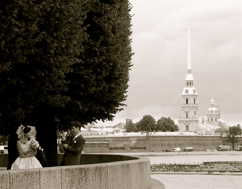 Saint Petersburg, Russia, 2008. A newlywed couple stops as the Peter and Paul Cathedral rises in the background. Summer is a popular time for wedding and countless newlyweds could be seen as we toured St. Petersburg.