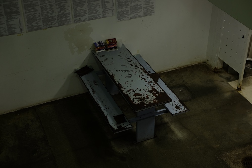 """El Mexicano"" is carved into a table in c-block, one of the all-female dorms. The flaking paint on the tables smells and has been giving the inmates headaches, the women said. Christmas Day, 2015."