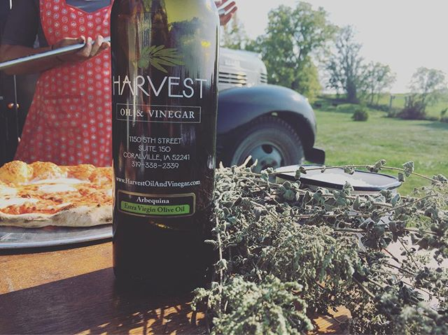 Some of that liquid green from the good folks at @harvestoilandvinegar. And look at that apron! 👀🍕 . . . #aprongameisstrong #woodfiredpizza #eatiowacity #oregano #42dodge