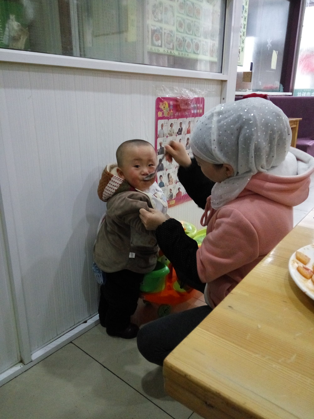 At another Muslim restaurant I watch a young mother wrangle in her son for dinner time.
