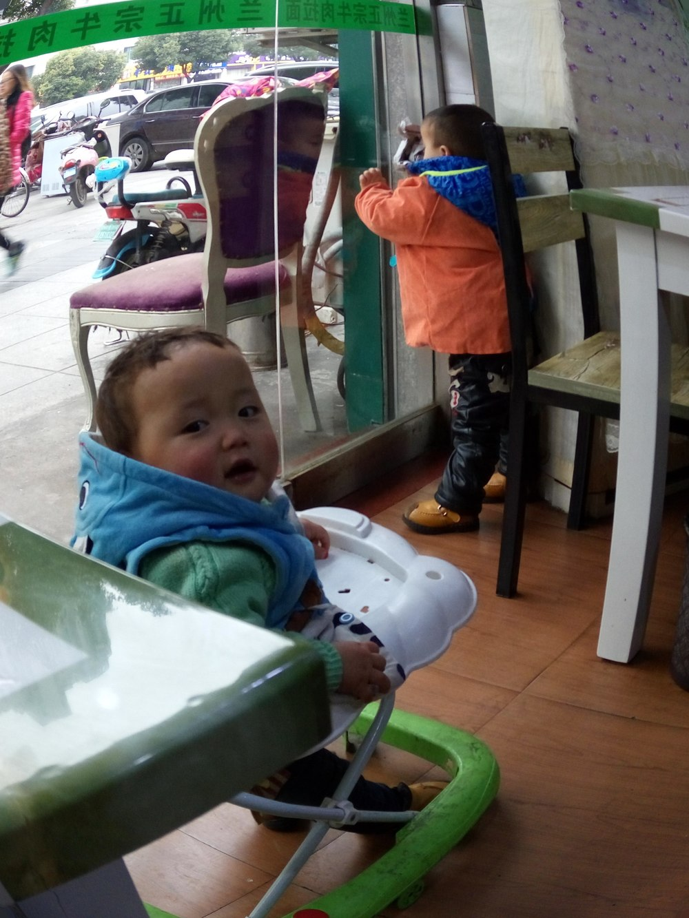 The noodle maker's baby bounces about while the owner's son looks out.