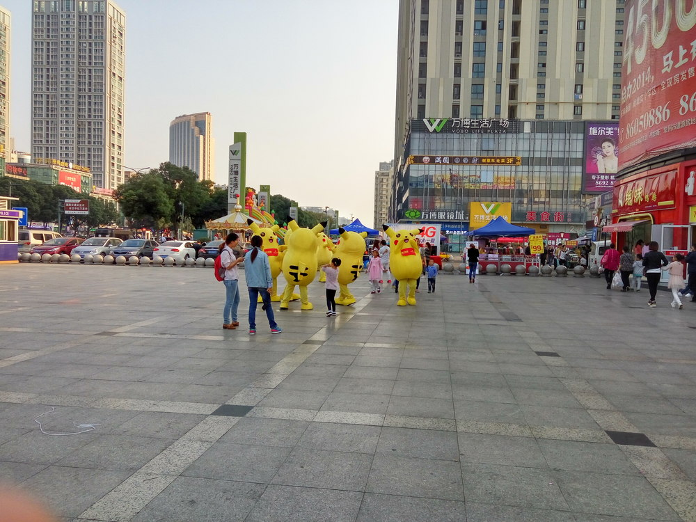 A gaggle of Pikachus entertain a few children.