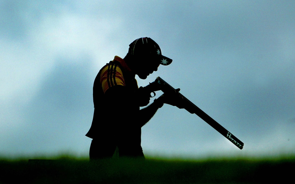 Australian trap shooter Michael Diamond blows down his rifle while competing in the 2002 Commonwealth Games. Diamond won the gold medal and compatriot Adam Vella won the silver medal.  Image supplied by Action Images/ Kieran Doherty.