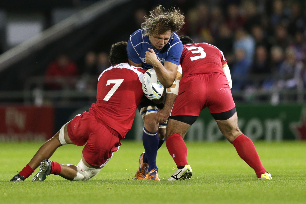 Namibia's Tinus du Plessis (C) suffers a double hit from Georgia's Davit Zirakashvili and Vito Kolelishvili during the 2015 Rugby World Cup. Tackles like this have become more common in rugby but could be causing long term negative affects. Image supplied by Action Images/ Henry Browne.
