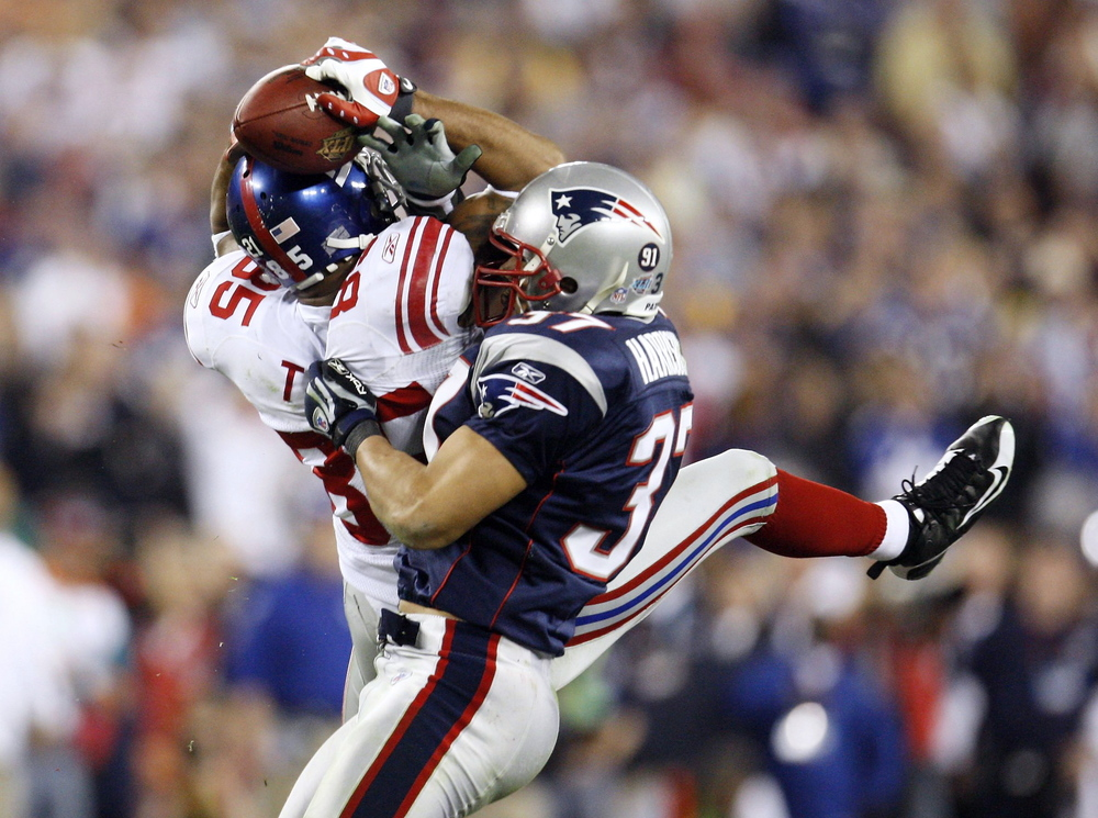 New York Giants receiver David Tyree (L) hauls in a Eli Manning (not pictured) pass last in the fourth quarter for a first down during the NFL's Super Bowl XLII. This victory is regarded as one of the greatest upsets of all time as the Patriots were chasing a perfect season and were expected to win the final comfortably.  Image supplied by Action Images/ Shaun Best.