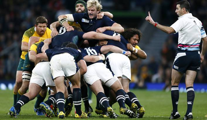 Craig Joubert (R) looks on as the Scottish and Australian packs wrestle for control in their quarter-final clash at the 2015 Rugby World Cup. Joubert has come under fire for his controversial decision to award Australia a penalty in the dying seconds of the match.  Reuters / Stefan Wermuth