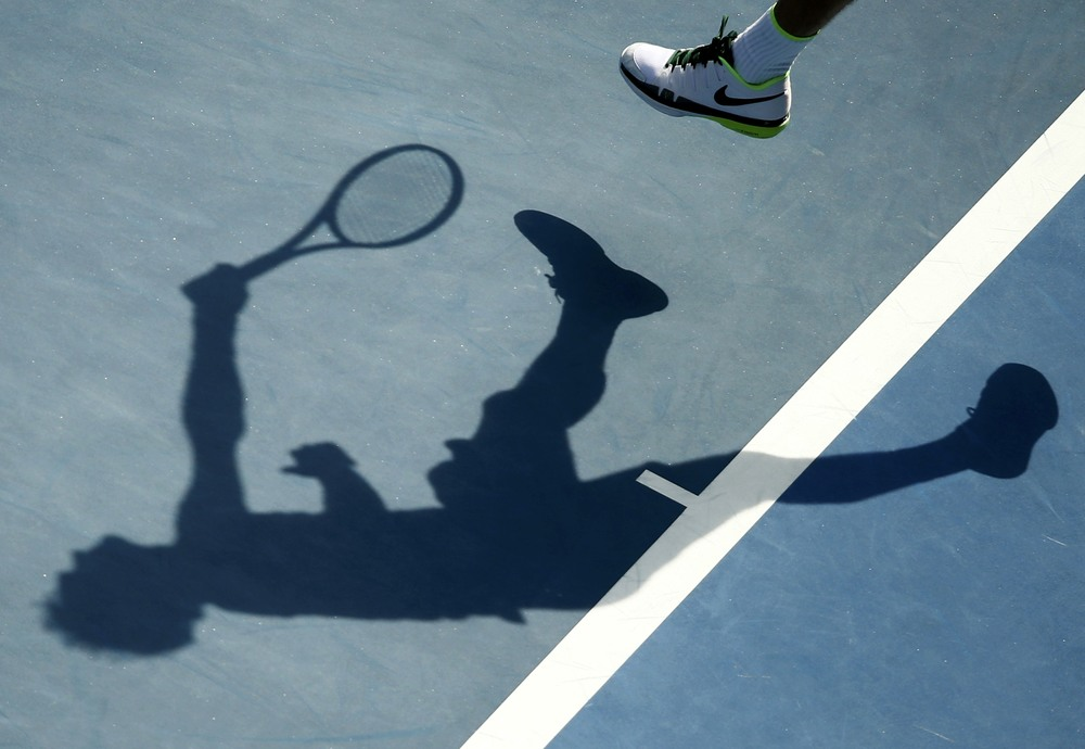 Roger Federer casts a shadow as he serves in the 2016 Australian Open. After damning allegations of match-fixing have rocked the integrity of world tennis, the future of the sport remains in the dark.  Image supplied by Action Images.