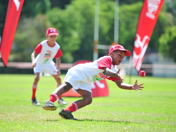 A young boy dives for a catch while competing in KFC Mini-Cricket. The organisation provides the first steps into cricket, not only for young boys and girls, but for coaches as well.