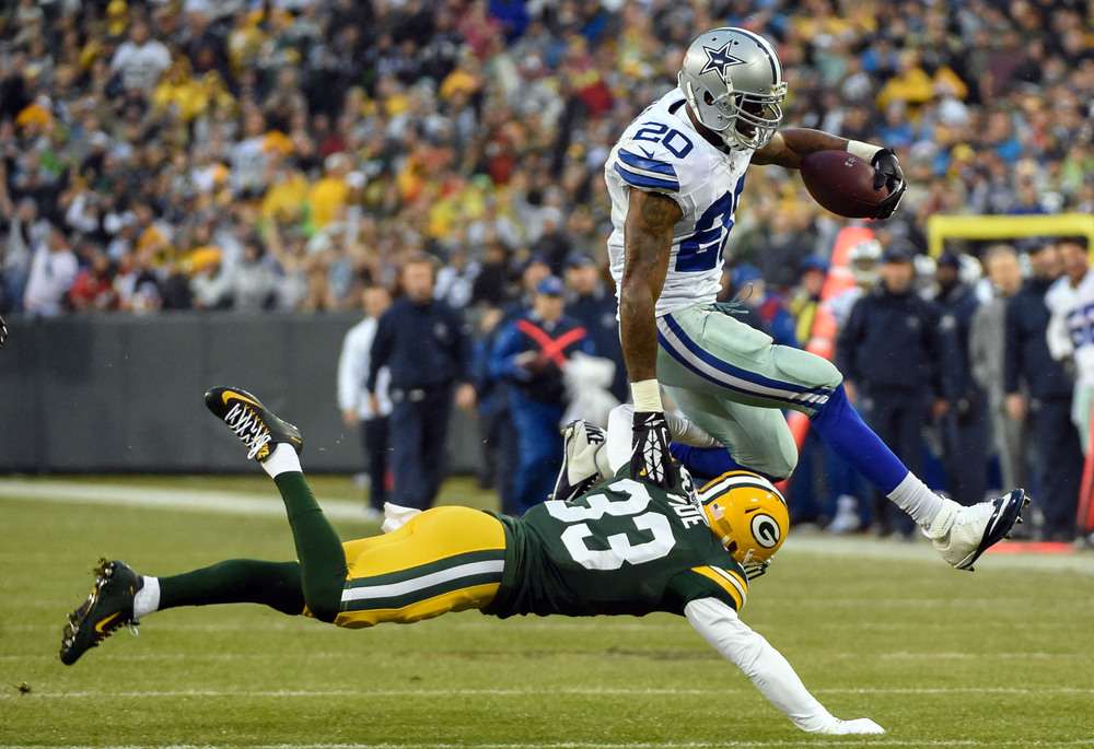 Darren McFadden (20), running back for the Dallas Cowboys, jumps over Green Bay Packers safety Micah Hyde (33). McFadden, like most elite athletes, is at his best when not over thinking his movements.  Image supplied by Action Images / Benny Sieu.