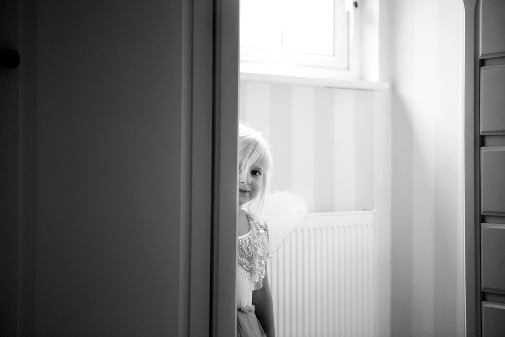 little girl peeping from behind wardrobe - At Home Photographer Essex