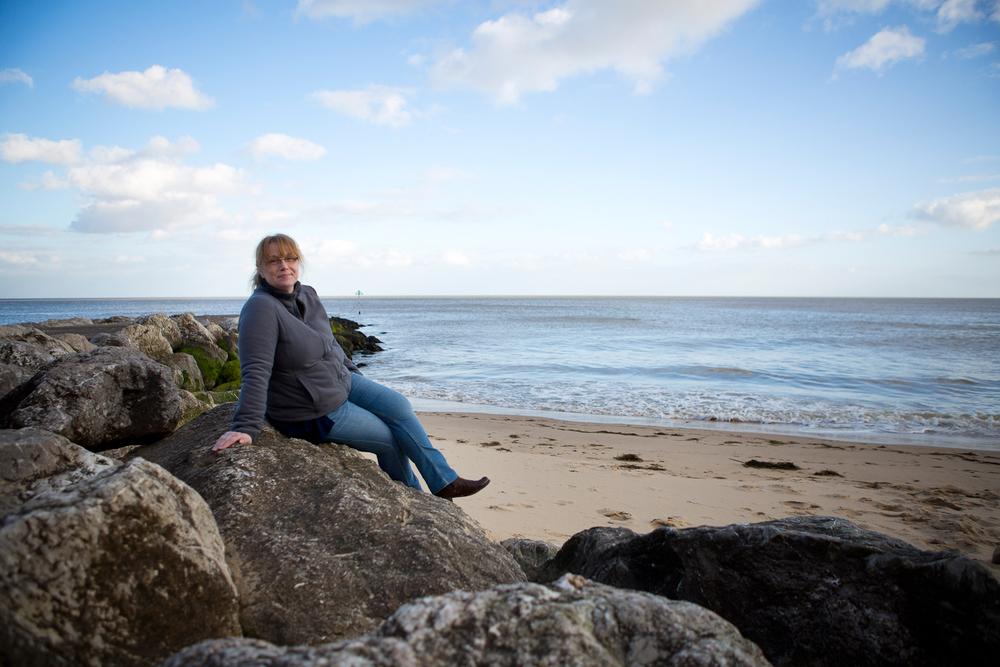lady sitting on rocks at walton on naze