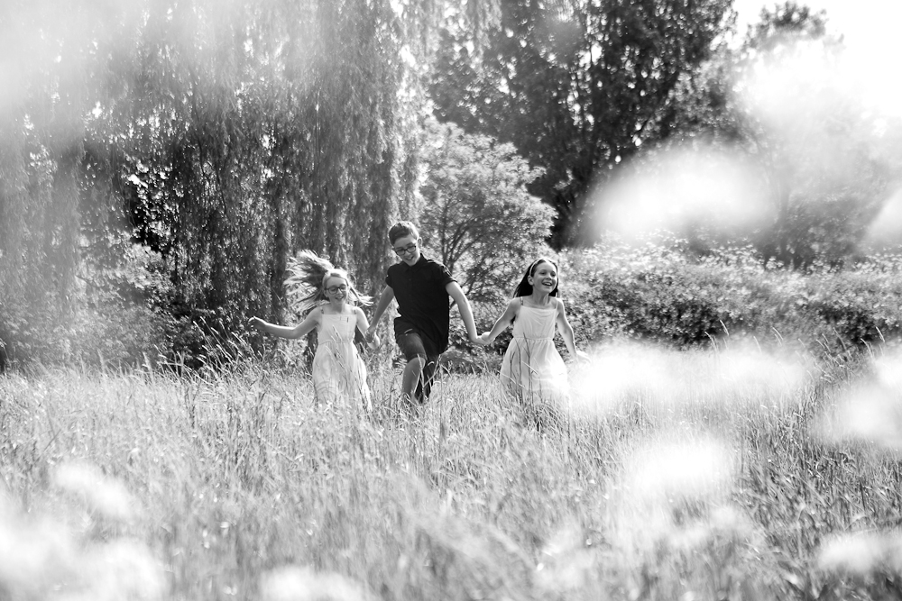brother and sisters running in field - chelmsford family photography