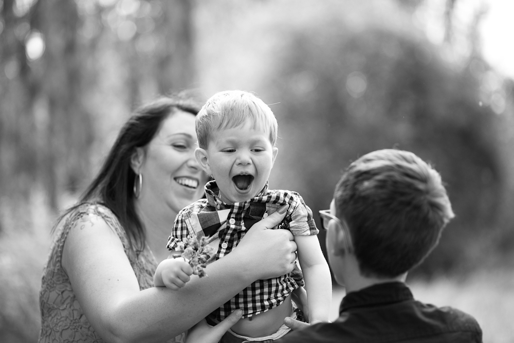 toddler laughing with mum and brother