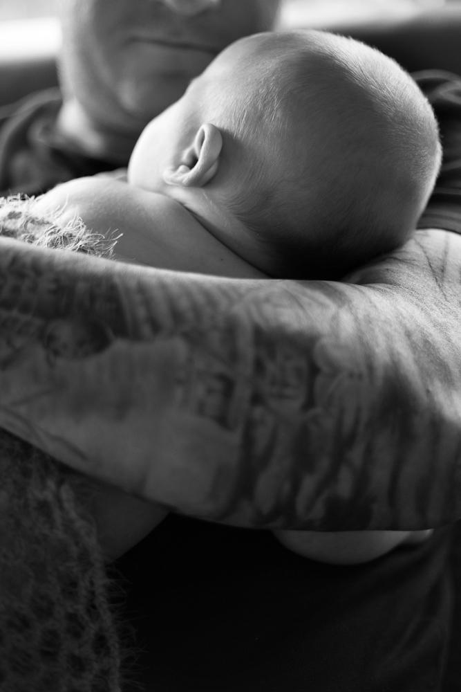 back of baby head asleep on tattoo arm