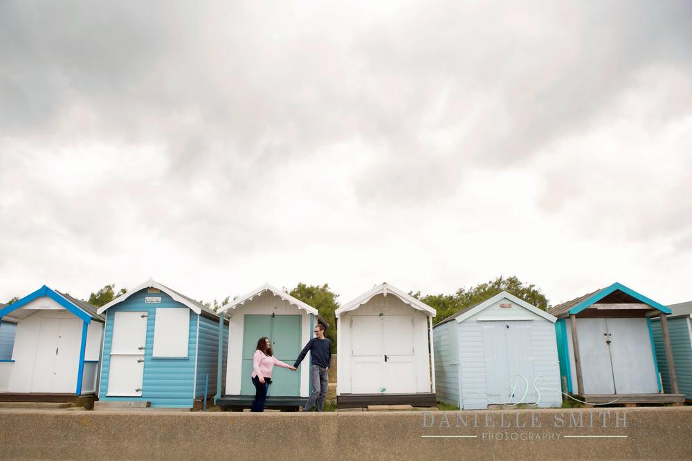 couple walking along in front of colourful beach huts