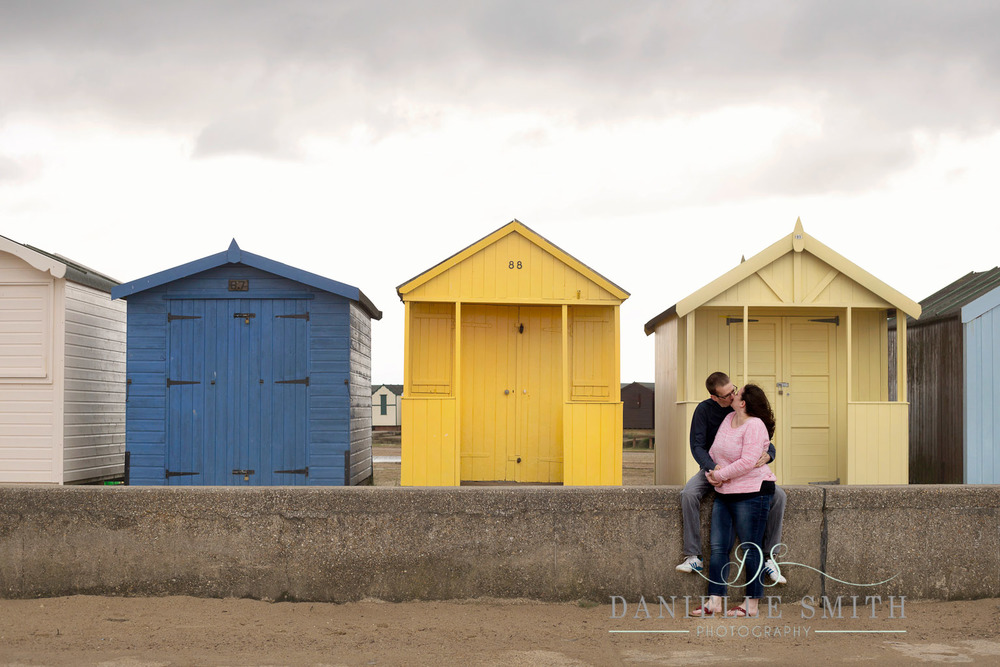 couple kissing in front of colourful beach huts