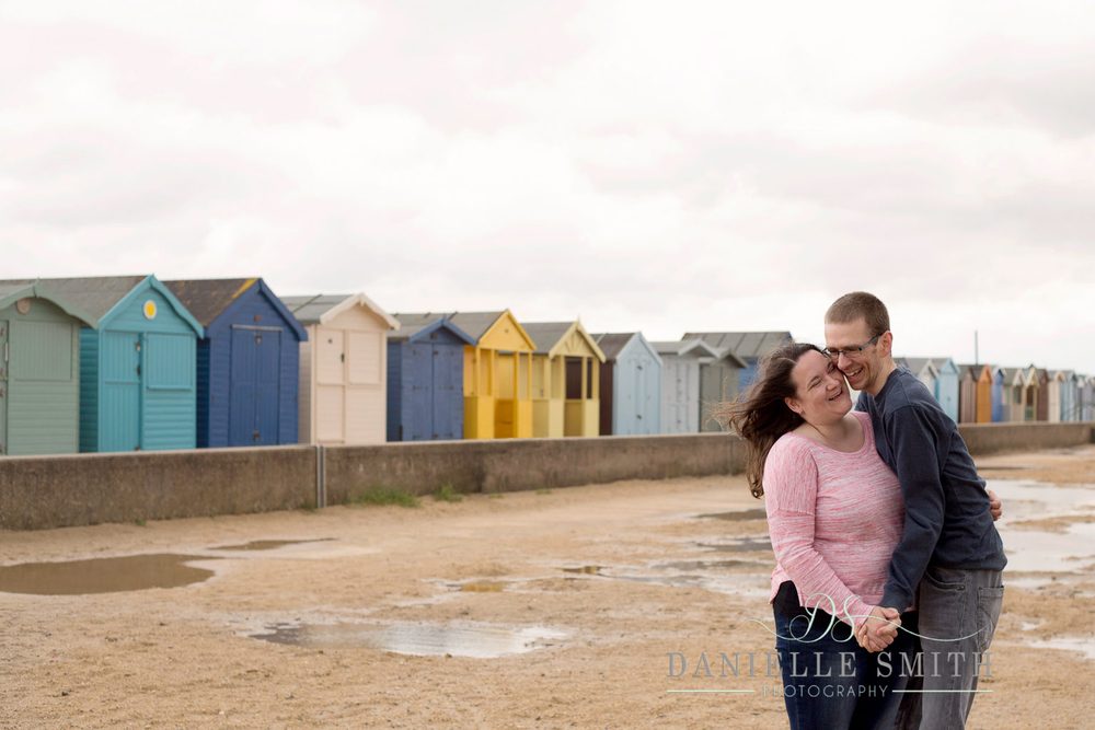 couple laughing on beach - seaside engagement photo shoot