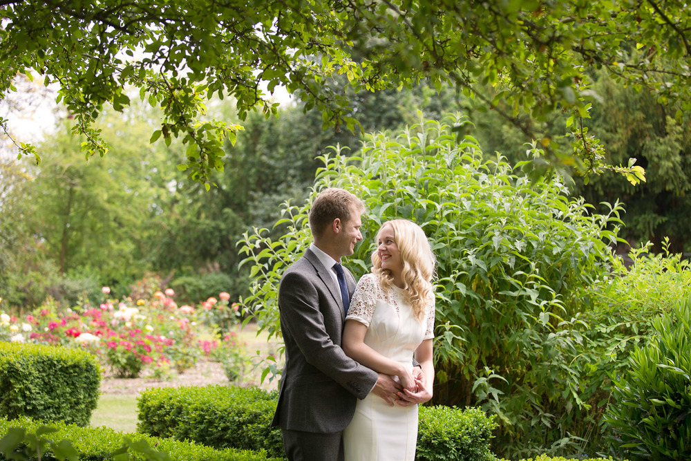 bride and groom cuddling in gardens