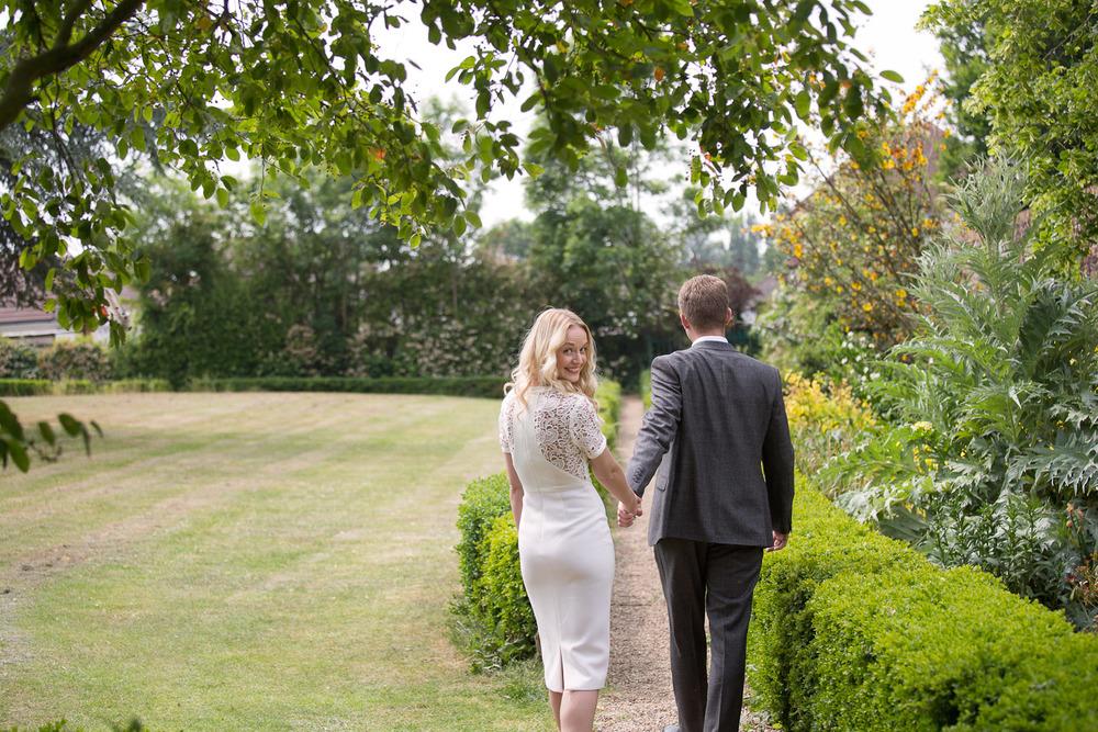 bride and groom walking away in garden wedding