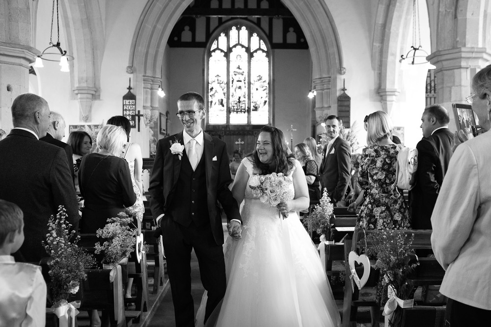 bride and groom walking down aisle in church
