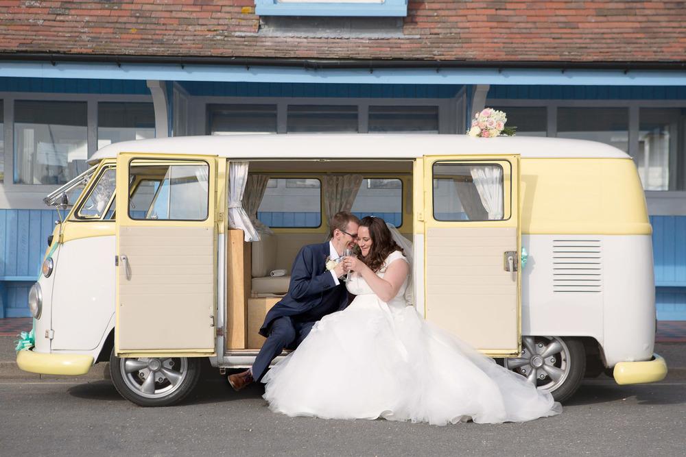 bride and groom sitting in camper van