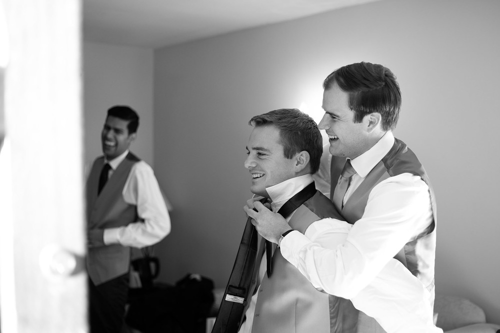 groom and best man putting ties on