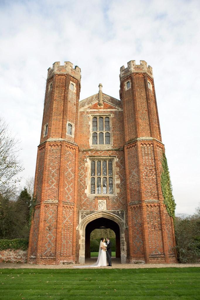 Bride and groom under tower at Leez Priory