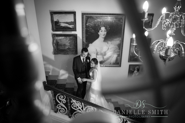 bride and groom through bannister at down hall wedding
