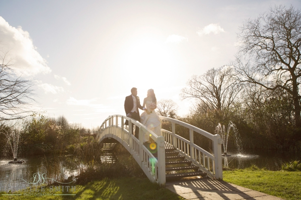 bride and groom walking over bridge with sun