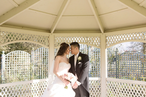 bride and groom under pergola