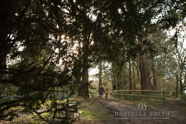 couple walking through woods in distance - pre-wedding photography