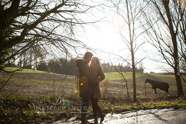 couple with horse in field behind