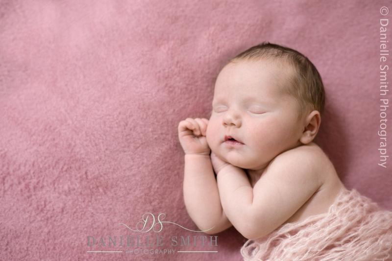 baby girl asleep on pink background