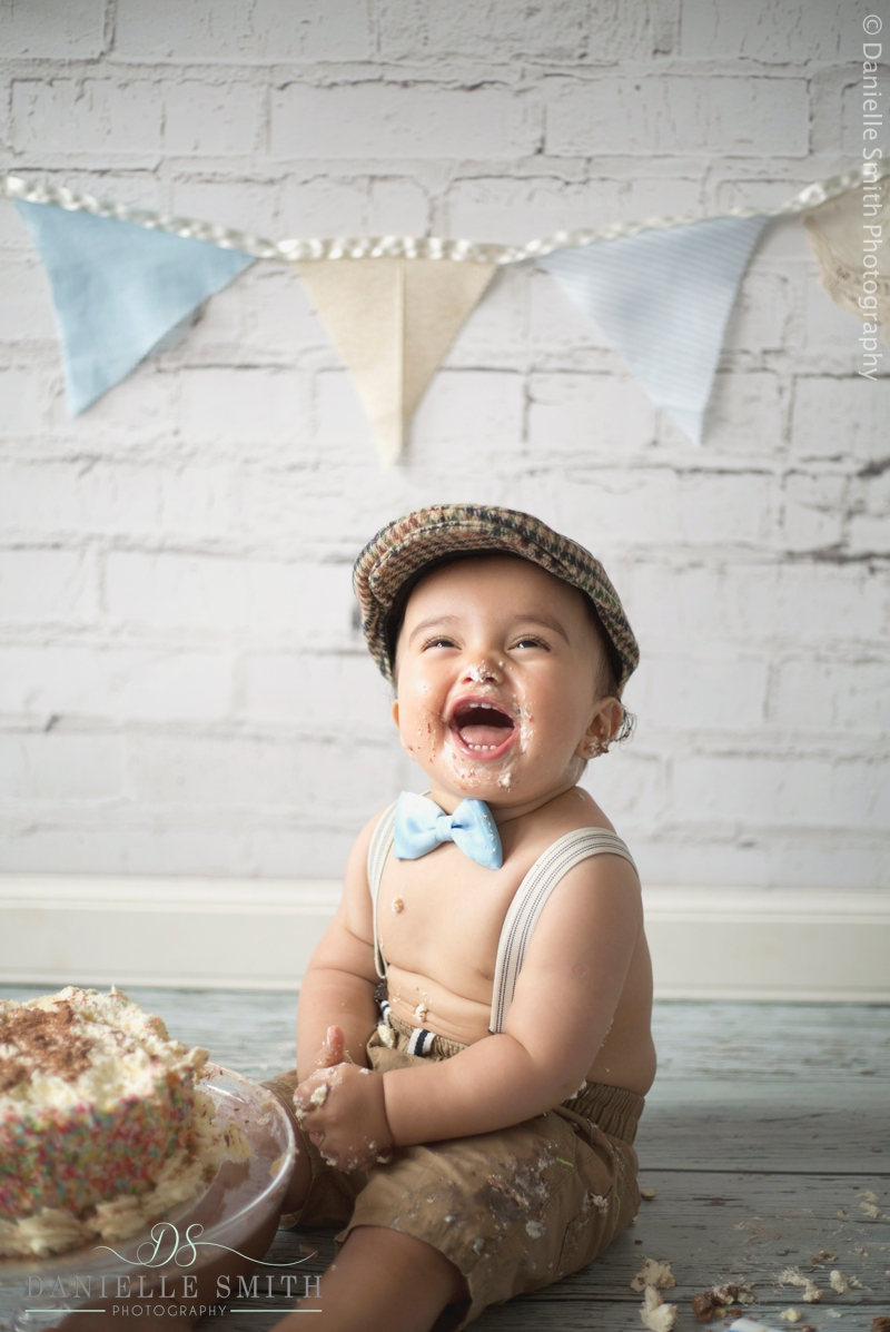 little boy laughing with cake over face