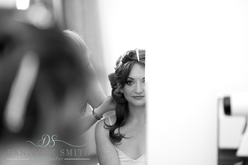 bride having hair done in mirror