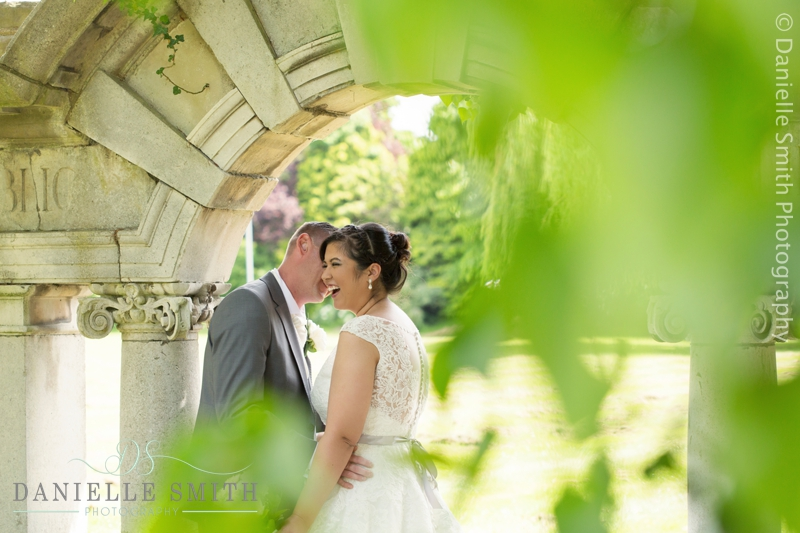 bride and groom laughing under arch
