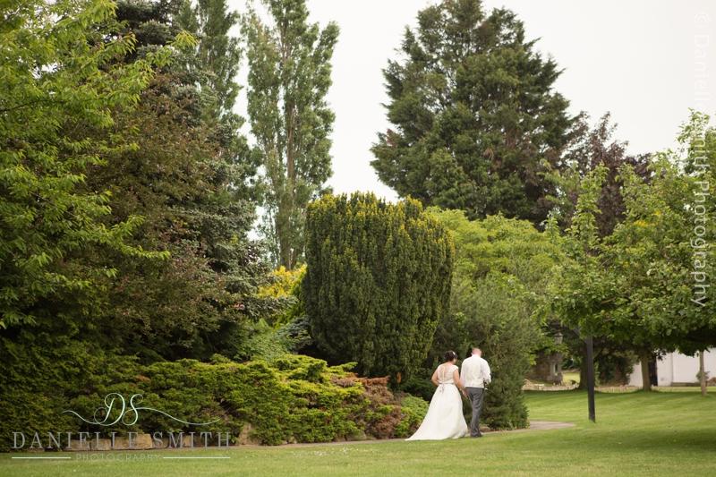 bride and groom walking into gardens