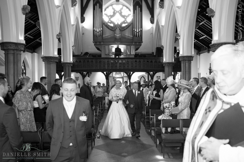 bride and dad walking down church aisle
