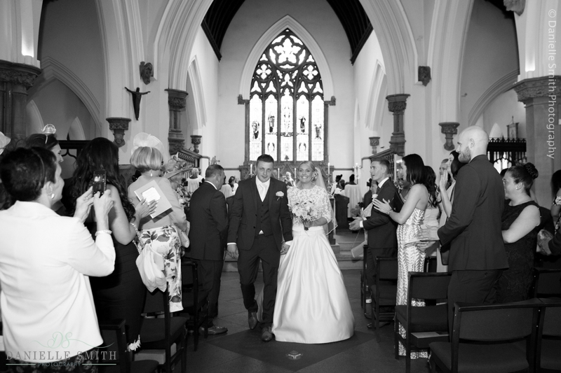 bride and groom walking down church aisle