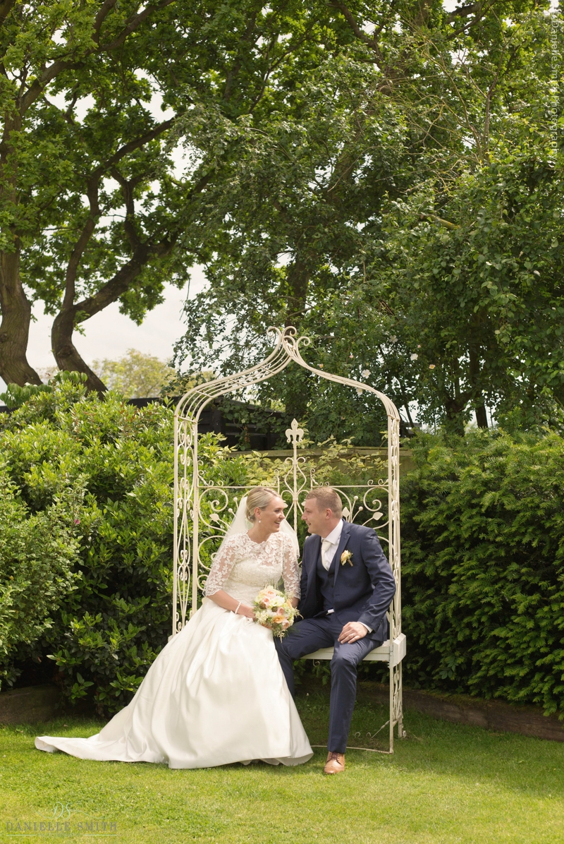 bride and groom sitting on ornate bench at maidens barn wedding