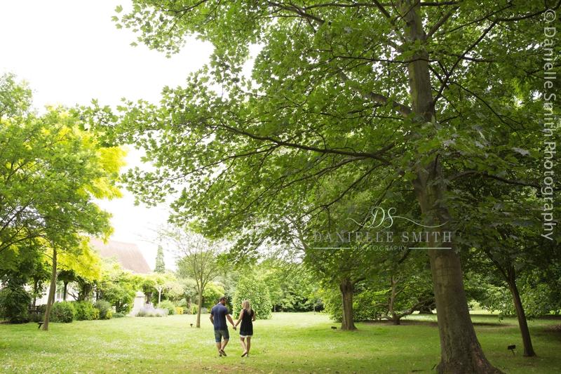 couple walking under tree in park