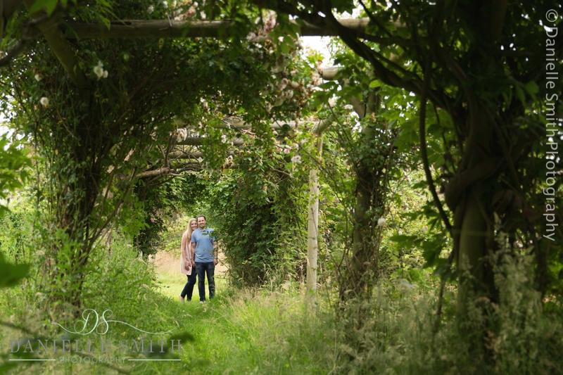 couple standing in garden pergola
