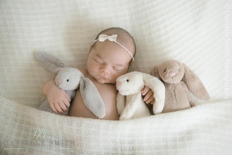 baby girl cuddling her bunnies in bed