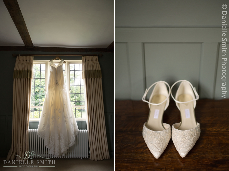 wedding dress hanging in front of window and shoes