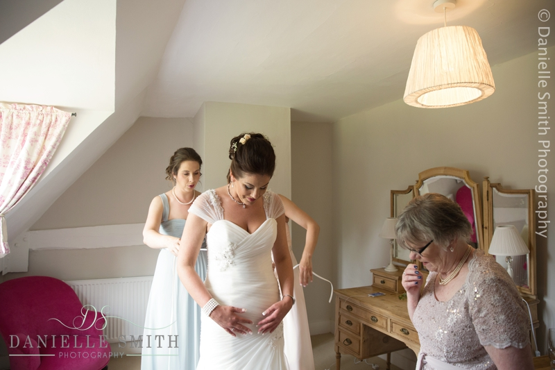 bridesmaids doing back of wedding dress up