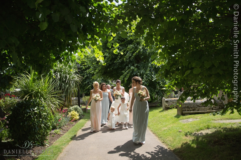bride and bridesmaid walking towards church - creative documentary wedding photography