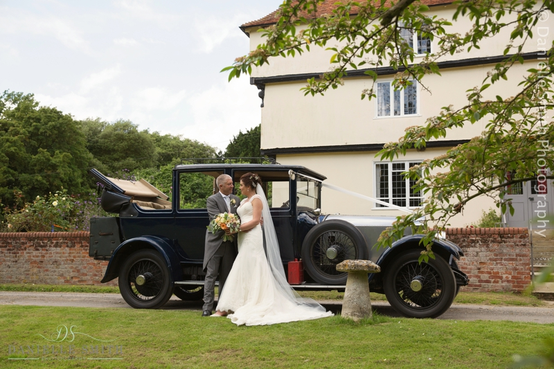 bride and groom with vintage car outside houchins wedding venue