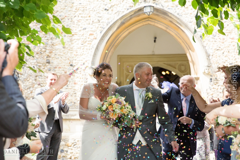 guests throwing confetti over bride and groom outside church