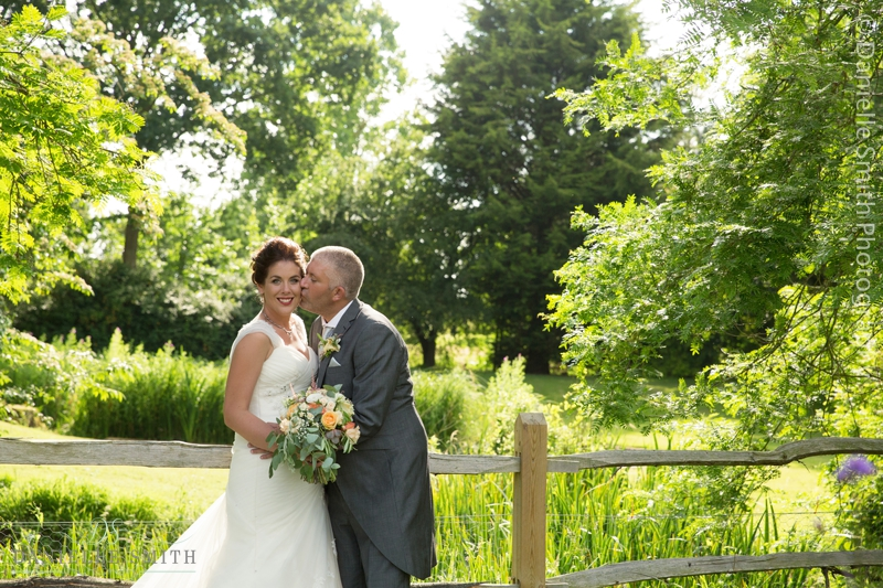 groom kissing his wife on cheek in gardens - houchins wedding photography
