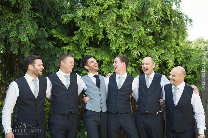 groom and groomsmen laughing in garden